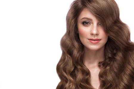 Hermosa chica de cabello castaño con un cabello perfectamente rizado y maquillaje clásico. Belleza de rostro y cabello. Cuadro admitido en el estudio. Foto de archivo