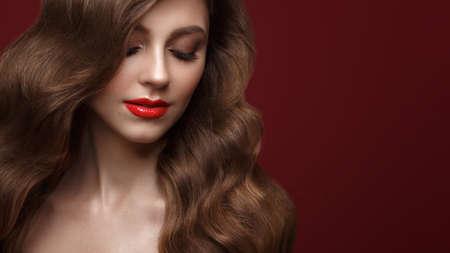 Mooi bruinharig meisje met perfect krullend haar en klassieke make-up. Schoonheid gezicht en haar. Foto gemaakt in de studio.