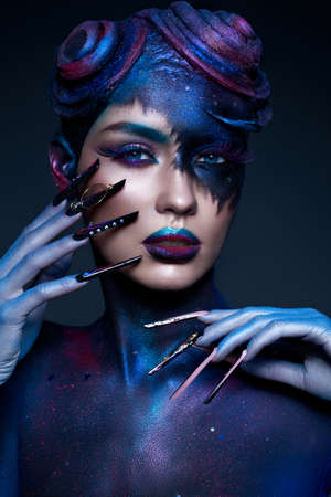 Beautiful girl with art fashion make-up, creative hairstyle, long nails. Design manicure. Beauty face. Picture taken in the studio.