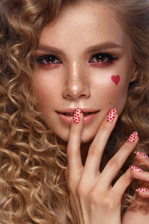 Pretty girl with curls hairstyle, classic makeup, freckles, nude lips and manicure design. Beauty face. Art nails. Studio portrait