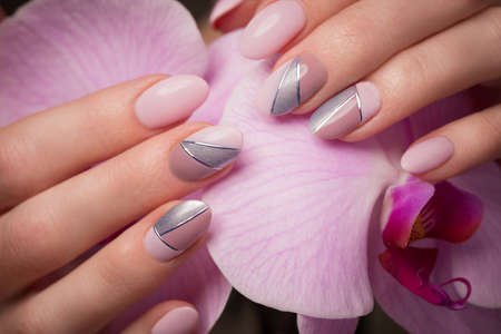 Purple neat manicure on female hands on a background of flowers. Nail design Stock Photo