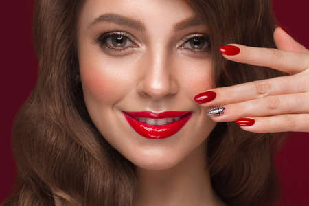 Beautiful girl with a classic make up, curls hair and multi-colored nails. Manicure design. Beauty face. Photo taken in the studio