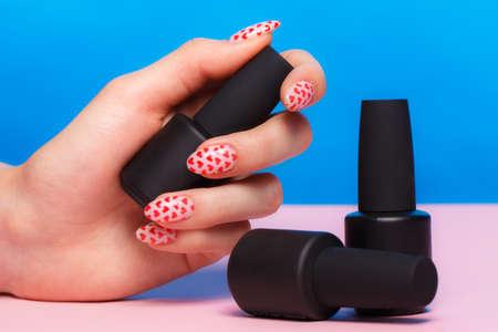 Botellas negras de esmalte de uñas sobre un fondo de colores. Diseño de manicura Foto de archivo