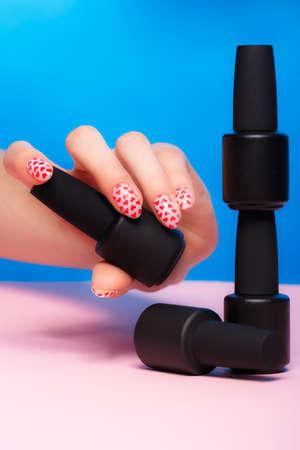 Black bottles of nail polish on a colorful background. Manicure design