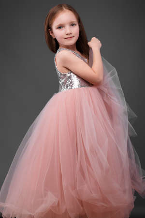 Little girl in a pink dress, with a beautiful hair. Photo taken in studio