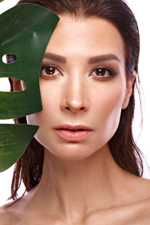 Beautiful fresh woman with perfect skin, natural make up and green leaves. Beauty face. Photo taken in the studio.