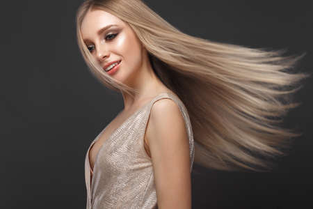 Beautiful blond girl in move with a perfectly smooth hair, and classic make-up. Beauty face. Picture taken in the studio. Stok Fotoğraf