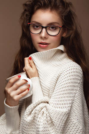 Beautiful girl in a cozy sweater with a cup of tea , glasses for vision and sexy lips. Beauty face. Photo taken in the studio