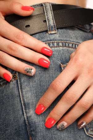 Bright neon red manicure on female hands on the background of jeans. Nail design. Beauty hands 免版税图像