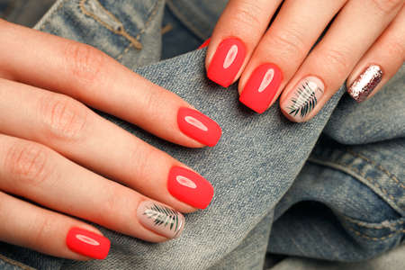 Bright neon red manicure on female hands on the background of jeans. Nail design. Beauty hands Stok Fotoğraf