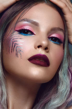 Beautiful girl with multi-colored hair and creative make up and hairstyle. Beauty face. Photo taken in the studio