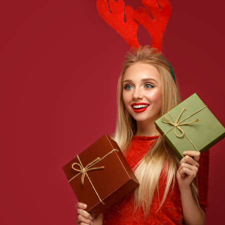 Beautiful blonde girl in a New Years image with boxes of gifts in hands and deer horns on her head. Beauty face with festive makeup. Photo taken in the studio. Stok Fotoğraf