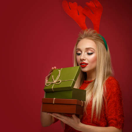 Beautiful blonde girl in a New Years image with boxes of gifts in hands and deer horns on her head. Beauty face with festive makeup. Photo taken in the studio. Stock Photo