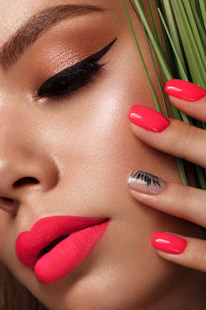 Beautiful young woman with bright makeup and neon pink nails. Beauty face. Photo taken in the studio.