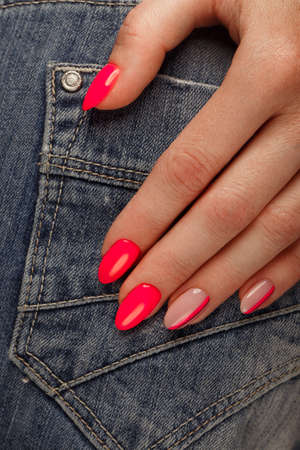 Bright neon manicure on female hands on the background of jeans. Nail design. Beauty hands