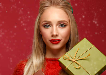 Beautiful blonde girl in a New Years image with boxes of gifts in hands. Beauty face with festive makeup. Photo taken in the studio.