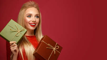 Beautiful blonde girl in a New Years image with boxes of gifts in hands. Beauty face with festive makeup. Photo taken in the studio. Stock Photo