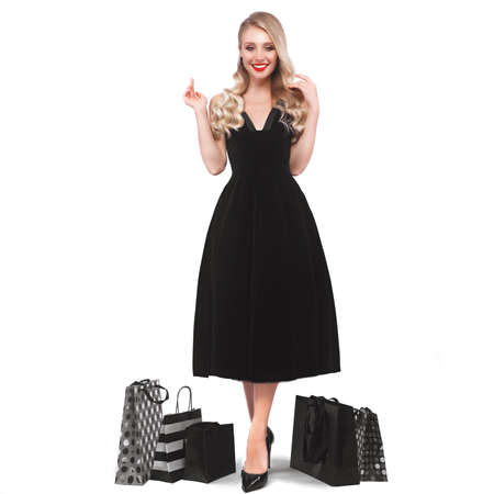 Beautiful girl with Hollywood locks, classic make-up, red lips in a black elegant dress and shopping bags. Beauty face and body. Photo taken in studio on a white background. Imagens