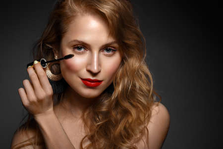 Schönes Mädchen mit roten Lippen und klassischem Make-up und Locken mit Wimperntusche in der Hand. Schönheitsgesicht. Foto im Studio aufgenommen. Standard-Bild