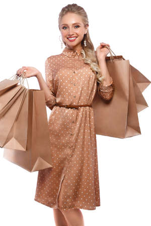 Beautiful girl with blond hair, classic make-up in a elegant dress and shopping bags. Beauty face and body. Photo taken in studio on a white background.