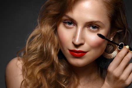 Hermosa chica con labios rojos y maquillaje clásico y rizos con rímel en la mano. Rostro de belleza. Foto tomada en el estudio.