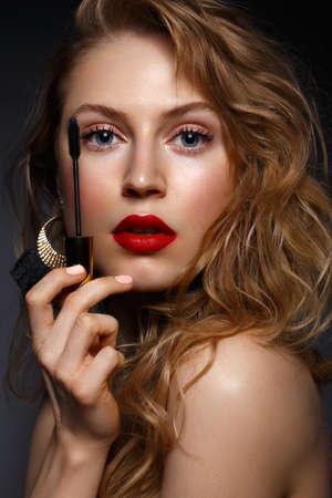 Schönes Mädchen mit roten Lippen und klassischem Make-up und Locken mit Wimperntusche in der Hand. Schönheitsgesicht. Foto im Studio aufgenommen.