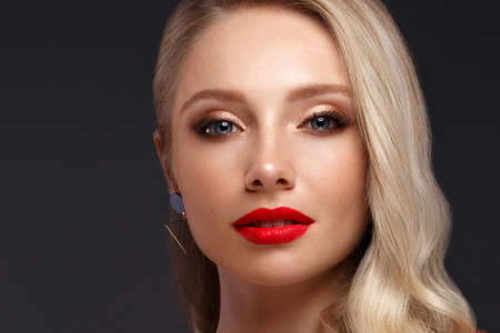Beautiful blonde in a Hollywood manner with curls, natural makeup and red lips.. Beauty face and hair. Picture taken in the studio Stock Photo