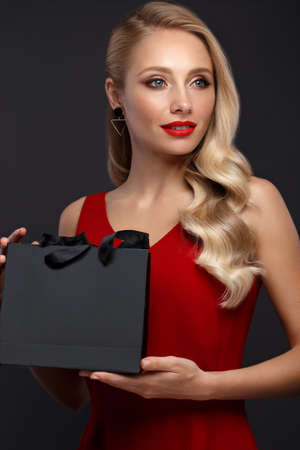Beautiful girl with blond hair, classic make-up in a elegant red dress and shopping bag. Beauty face. Photo taken in studio on a white background. Stock Photo