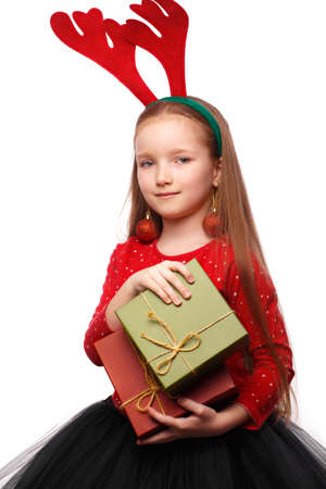 Beautiful little girl in a New Years image with boxes of gifts in hands and deer horns on her head. Photo taken in the studio.