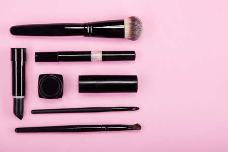Set of brushes and cosmetic products on a pink background.