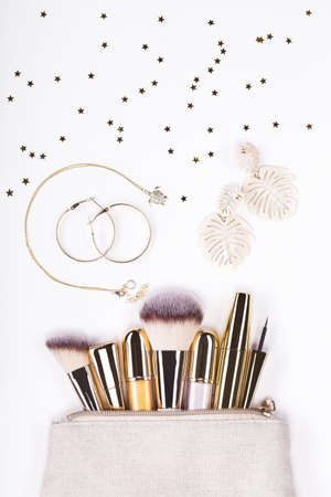 Set of brushes and cosmetic products in a cosmetic bag on a white background.