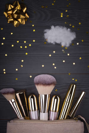 Set of brushes and cosmetic products in a cosmetic bag on a grey background. Zdjęcie Seryjne