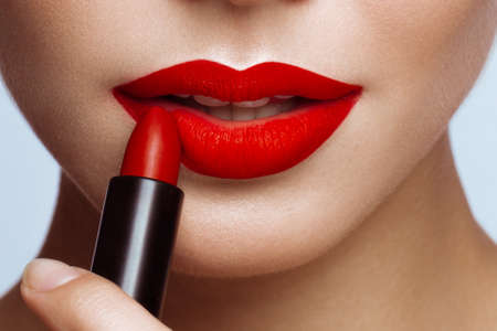 Beautiful girl with red lips and classic makeup with lipstick in hand. Beauty face. Photo taken in the studio. Imagens