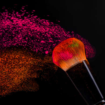 Cheek brush with neon cosmetic powder colorful spray and isolated on black background
