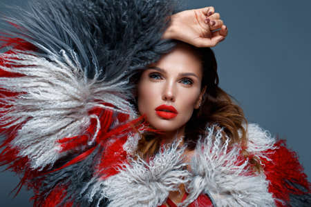Beautiful woman with classic holiday make-up, red lips, curls in a multi-colored llama coat. Beauty face. Photo taken in studio 스톡 콘텐츠