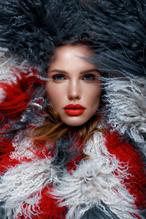 Beautiful woman with classic holiday make-up, red lips, curls in a multi-colored llama coat. Beauty face. Photo taken in studio Banque d'images - 135465099