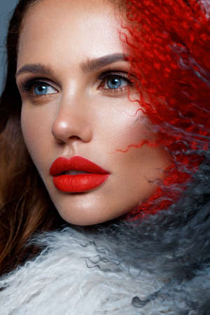 Beautiful woman with classic holiday make-up, red lips, curls in a multi-colored llama coat. Beauty face. Photo taken in studio Banque d'images - 135465109