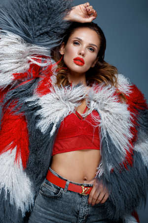Beautiful woman with classic holiday make-up, red lips, curls in a multi-colored llama coat. Beauty face. Photo taken in studio Banque d'images - 135465125