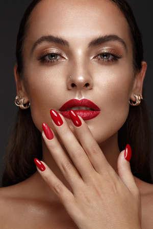Hermosa chica con un maquillaje clásico y uñas multicolores. Diseño de manicura. Cara de belleza. Foto tomada en el estudio. Foto de archivo