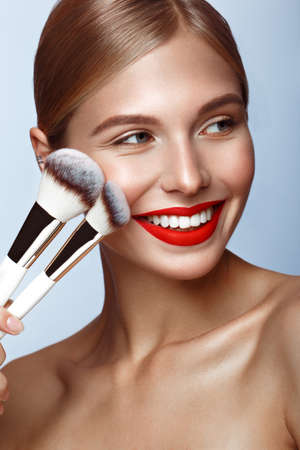 Beautiful girl with red lips and classic makeup with cosmetic brushes in hand. Beauty face. Photo taken in the studio.
