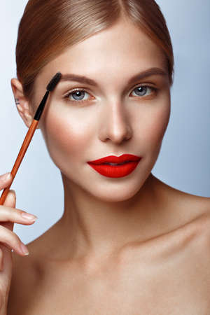 Beautiful girl with red lips and classic makeup with cosmetic brow brush in hand. Beauty face. Photo taken in the studio.