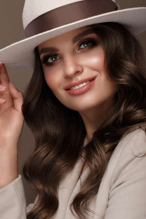 Beautiful woman in a fashionable hat, with classic make-up, wave hair and smile. Beauty face. Photo taken in the studio.