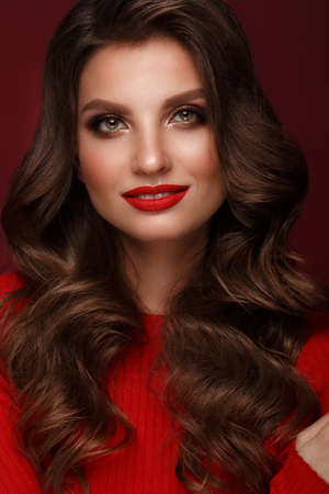 Beautiful woman with classic make-up, wave hair and red lips. Beauty face. Photo taken in the studio.