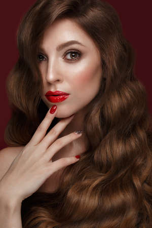 Beautiful girl with a classic make up, curls hair and red nails. Manicure design. Beauty face. Photo taken in the studio