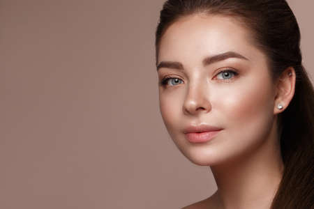 Beautiful young girl with natural make-up with cosmetic in hands. Beauty face. Photo taken in studio