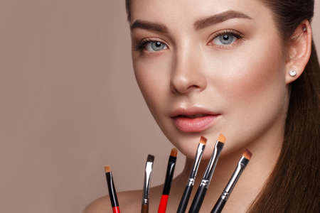 Beautiful young girl with natural make-up with cosmetic tools in hands. Beauty face. Photo taken in studio