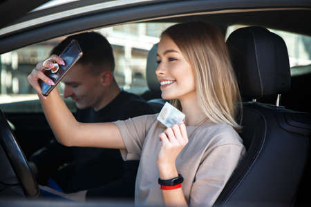 Happy smiling girl takes a selfie with a new drivers license, sitting next to an instructor. Stok Fotoğraf
