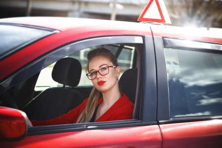 Young beautiful happy woman in red sitting at the wheel new training car