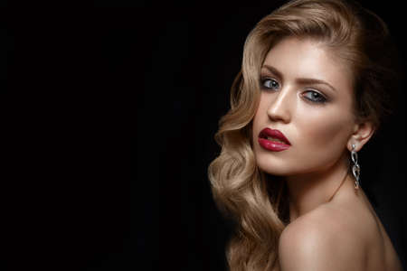 Beautiful girl with red lips and classic makeup and curls. Beauty face. Photo taken in the studio.