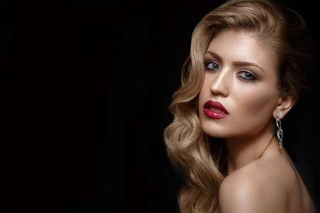 Belle fille aux lèvres rouges et maquillage classique et boucles. Beau visage. Photo prise en studio.